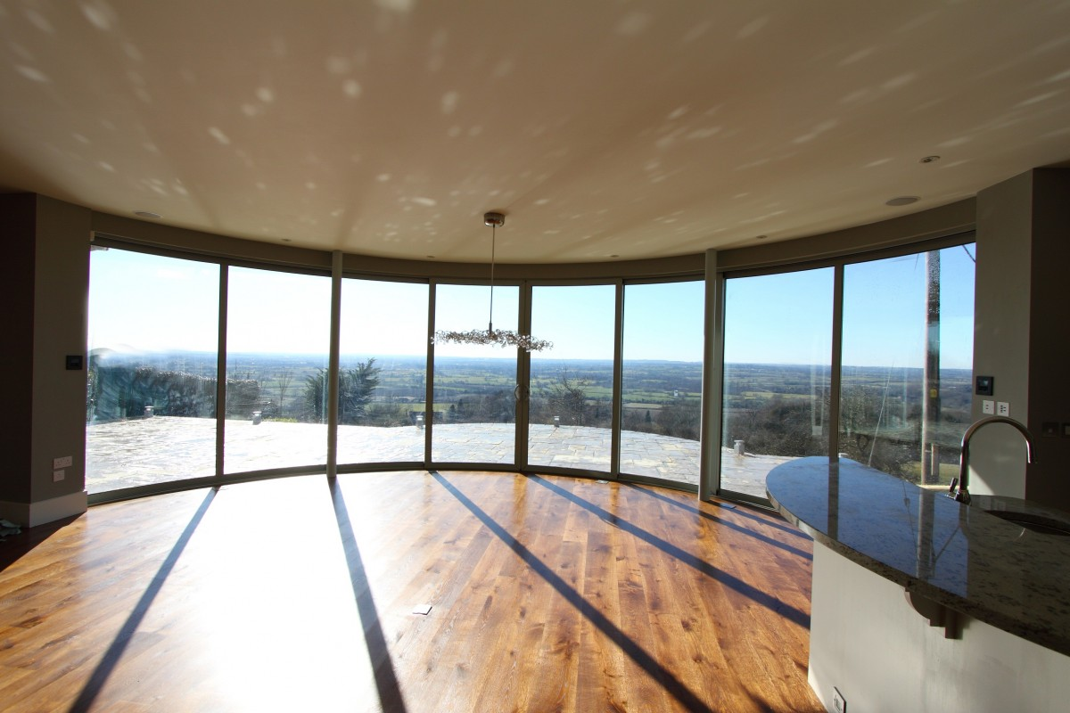 Curved sliding glass doors with panoramic views for Floor to ceiling folding glass doors